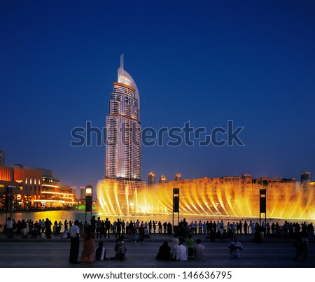 DUBAI, UAE - JUL3 : The Dubai Fountain on Jul 3, 2013 in Dubai. Dubai's best attraction, with 6600 lights, 275 m long and shoots water up to 150 m into the air accompanied by a range of world music - stock photo
