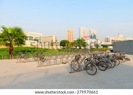DUBAI, UAE - 16 JULY 2014: Bicycle racks provide a secure place to park dozens of bikes to encourage alternative transportation in this modern and progressive city. - stock photo