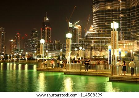 DUBAI, UAE - JUNE 7: The area with tourist near Burj Khalifa. It is the world's tallest skyscraper (height 828m, 160 floors) on June 7, 2012 in Dubai, UAE - stock photo