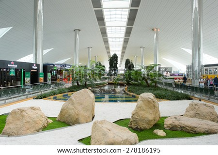 DUBAI, UAE - MARCH 10, 2015: DXB airport interior. Dubai International Airport is an international airport serving Dubai. It is a major airline hub in the Middle East, and is the main airport of Dubai - stock photo