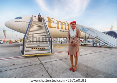 DUBAI, UAE - MARCH 31, 2015: Emirates crew member near Boeing-777. Emirates is one of two flag carriers of the United Arab Emirates along with Etihad Airways and is based in Dubai. - stock photo