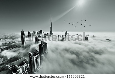 DUBAI, UAE - MAY 12: Burj khalifa, the highest building in the world, Downtown is covered by early morning fog on May 12,2013 in Dubai, UAE - stock photo
