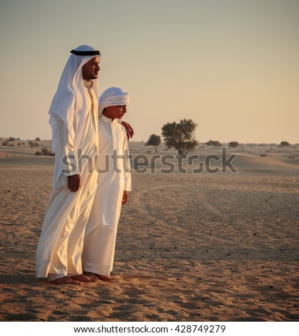 DUBAI, UAE - NOVEMBER 12, 2013: Arab man and a teenager in the desert and watch the sunset - stock photo