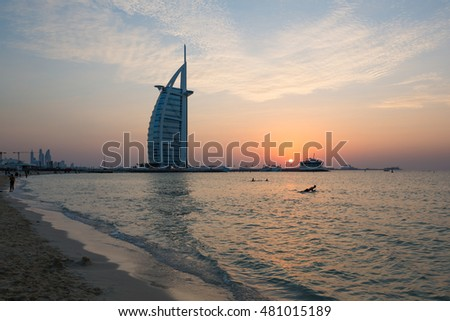 DUBAI, UAE - NOVEMBER 16, 2014: Dubai beach. Dubai sunset. Burj Al Arab the luxury seven star Dubai hotel at sunset. Dubai iconic hotel. Jumeirah hotel. Top hotels. Dubai best views. Dubai icon.