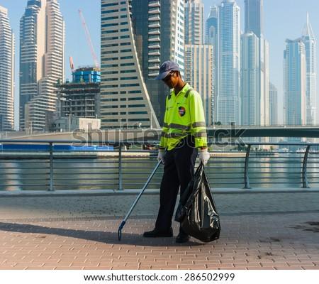 DUBAI, UAE - NOVEMBER 13, 2012: Dubai street cleaner - stock photo