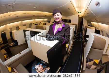 Dubai, UAE - NOVEMBER 09, 2015: Etihad Airways Airbus A380 cabin crew member, flight attendant. Smiling stewardess.  Etihad Airways Airbus A380 business class on November 09, 2015 in Dubai - stock photo