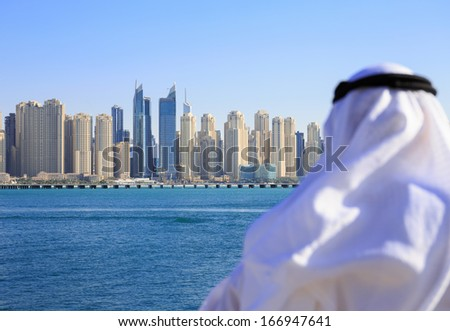 DUBAI, UAE - NOVEMBER 7: General view of the Dubai Marina, on November 7, 2013, Dubai, UAE. In the city of artificial channel length of 3 kilometers along the Persian Gulf. Man looks at the city - stock photo