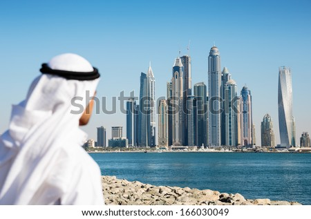 DUBAI, UAE - NOVEMBER 7: Modern buildings in Dubai Marina,, UAE. In the city of artificial channel length of 3 kilometers along the Persian Gulf. Man in Arab dress looks at the city - stock photo