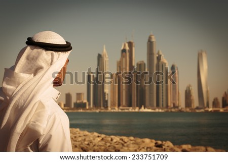 DUBAI, UAE - NOVEMBER 7: Modern buildings in Dubai Marina,, UAE. In the city of artificial channel length of 3 kilometers along the Persian Gulf. Man in Arab dress looks at the city. Toned - stock photo
