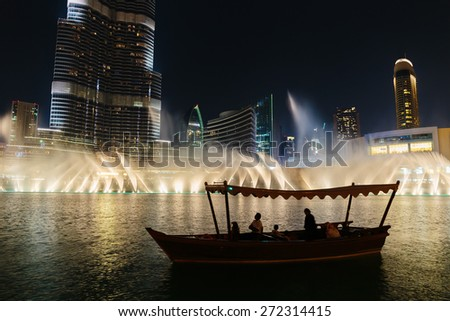 DUBAI, UAE - NOVEMBER 13: Night view Dancing fountains downtown and in a man-made lake in Dubai, UAE on November 13, 2013. The Dubai Dancing fountains are world's largest fountains with height 150 m. - stock photo