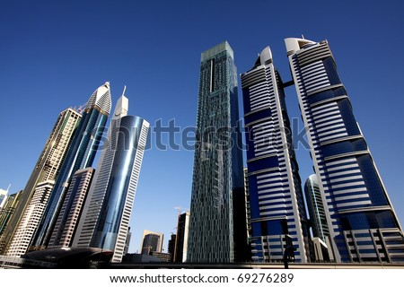 DUBAI, UAE - NOVEMBER 17: View at Sheikh Zayed Road skyscrapers in Dubai at November 17, 2010. More than 25 skyscrapers taller than 100 meters can be found there. - stock photo