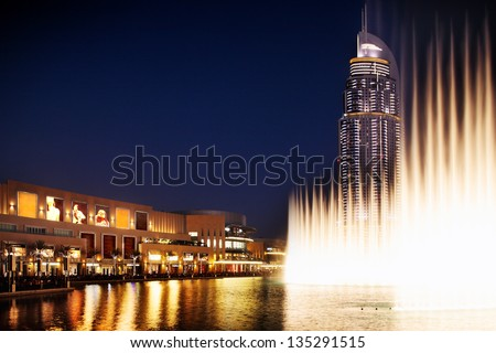 DUBAI, UAE - OCT 1: The Dancing Fountain of Dubai performs to the beat of the selected music at dusk on Oct 1, 2010 in Dubai, UAE. The fountain is overlooked by Dubai Mall and the Address Hotels - stock photo