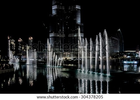 DUBAI, UAE - OCTOBER 1, 2012: Dubai Fountain is world largest choreographed fountain system set on Burj Khalifa Lake - 6600 lights and 25 colored projectors; it shoots water 152 m into the air. - stock photo