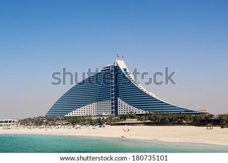 DUBAI, UAE - OCTOBER 10, 2012: Jumeirah Beach Hotel, Pyramid-shaped architecture work, next to famous Burj Al Arab, one of the well-known landmarks of Dubai, UAE. - stock photo