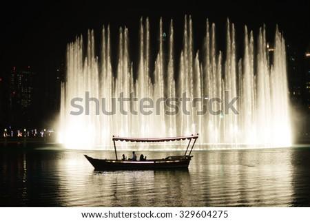 DUBAI, UAE - OCTOBER 15, 2014: The Dubai Fountain at night. The Dubai Fountain is the world's largest choreographed fountain system set on the 30-acre manmade Burj Khalifa Lake. - stock photo