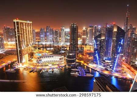 DUBAI, UAE - SEPTEMBER 8: The night illumination of Dubai Marina on September 8, 2013 in Dubai, UAE. It is an artificial canal city, built along a two mile (3 km) stretch of Persian Gulf shoreline. - stock photo