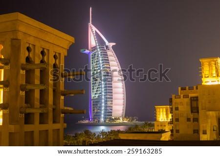 DUBAI, UNITED ARAB EMIRATES - CIRCA AUGUST 2014 - Beautifully lit Burj Al Arab seen from Madinat Jumeirah on a sweltering hot summer night - stock photo