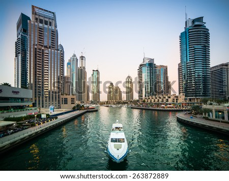 Dubai, United Arab Emirates - December 14, 2013: Modern skyscrapers and water channel with boats of Dubai Marina in evening, United Arab Emirates - stock photo