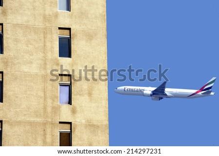 DUBAI, UNITED ARAB EMIRATES-FEBRUARY,10,2014;Airplane of Emirates Airline is taking off near apartment buildings in the city of Dubai. February 10,2014 Dubai - stock photo