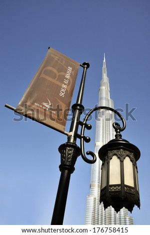 DUBAI,UNITED ARAB EMIRATES-FEBRUARY 07,2014; Arabic style lamp post together with flag of the Souk al Bahar with at the background famous icon Burj Khalifa.February,o7,2014 Dubai,United Arab Emirates. - stock photo