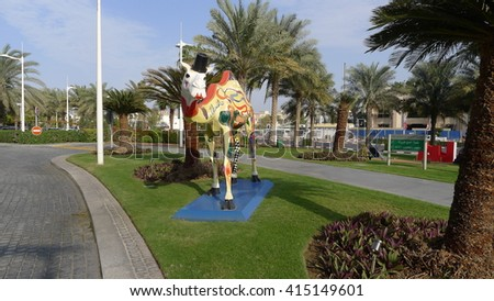 Dubai, United Arab Emirates - February 12, 2016 : Jumeirah Beach hotel surrounded by green palm trees on a sunny day. Creative decor with camel artworks display - stock photo