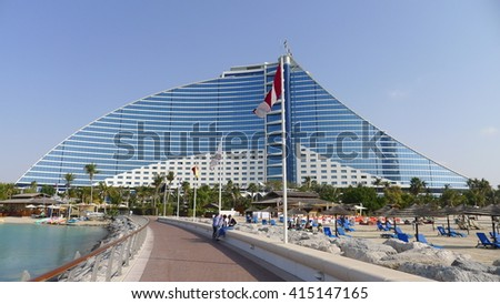 Dubai, United Arab Emirates - February 12, 2016 : Jumeirah Beach hotel with the pure white sand beach and crystal clear water surrounded by green palm trees. Voted the Best Hotel in the Middle East  - stock photo