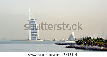 DUBAI, UNITED ARAB EMIRATES - FEBRUARY 9, 2014: View of Burj Al Arab hotel at the sea side. One of the world's most luxurious hotels with 7 stars. February 9, 2014 Dubai, United Arab Emirates  - stock photo
