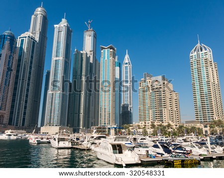 DUBAI, UNITED ARAB EMIRATES - JAN 25, 2014: Motor yachts and highrise buildings in the Marina district of Dubai, United Arab Emirates - stock photo