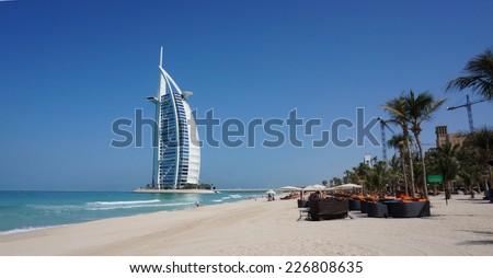 DUBAI, UNITED ARAB EMIRATES -OCTOBER 18, 2014: View of Burj Al Arab hotel from the Jumeirah beach. Burj Al Arab is one of the Dubai landmark, and one of the world's most luxurious hotels with 7 stars. - stock photo