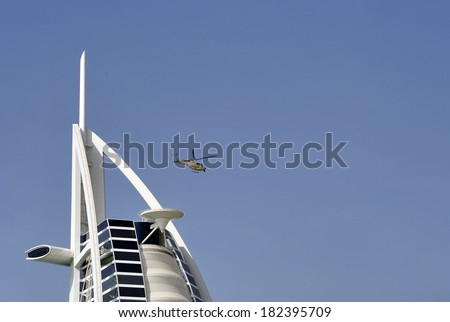 DUBAI UNITED EMIRATES - FEBRUARY 8, 2014: View of Burj Al Arab hotel with leaving helicopter from helicopter deck. February 8, 2014 Dubai - stock photo