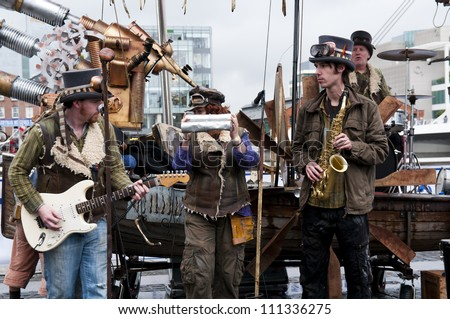 DUBLIN - AUGUST 24: A street performance band plays in the Dublin harbor on August 24, 2012 in Dublin, Ireland. It is one of the attractions in the Tall Ships Race. It is a unique band plays on scrap. - stock photo