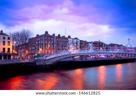 Dublin Ireland at dusk with waterfront and historic Ha'penny Bridge  - stock photo