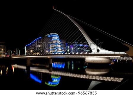 DUBLIN, IRELAND - AUGUST 23: Samuel Beckett Bridge, a cable-stayed bridge by architect Santiago Calatrava, pointing to Dublin Convention Center at nighttime, on August 23, 2011 in Dublin, Ireland - stock photo