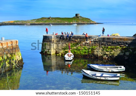 DUBLIN, IRELAND - CIRCA JUNE: Coliemore Harbour with Dalkey Island in the background circa June, 2013 in Dalkey, Ireland. The Martello fort on the island was built in 1804. - stock photo