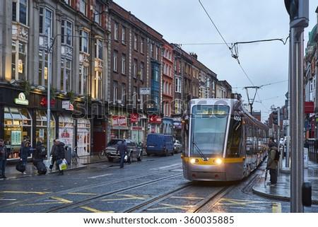 DUBLIN, IRELAND - JANUARY 05: The Luas, Dublin's tram system train, crossing pedestrian area in rainy day. January 05, 2016 in Dublin - stock photo