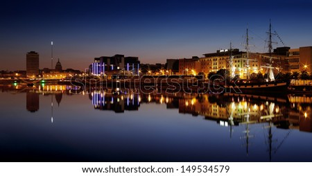 DUBLIN, IRELAND - JULY 22: Dublin City Center reflecting in the River Liffey on July 22, 2013 in Dublin, Ireland. The River Liffey in Dublin has been used for many centuries for trade and commuting. - stock photo