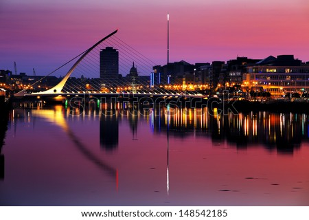 DUBLIN, IRELAND - JULY 22: North bank of the river Liffey at Dublin City Center at night with Samuel Beckett Bridge and The Spire as seen from the south bank on July 22, 2013 in Dublin, Ireland - stock photo