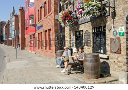 DUBLIN, IRELAND - JUNE 8: Family rests on bench in front of the oldest pub in Ireland,     The Brazen Head, Dublin, Ireland on June 8, 2013 - stock photo