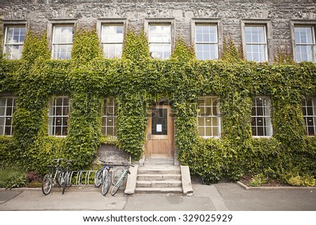 DUBLIN, IRELAND - JUNE 19, 2010: The entrance to a building is covered with ivy on the Trinity College campus in Dublin. Students' bicycles are parked in a bike rack by the entry steps. - stock photo