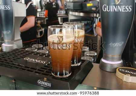 DUBLIN, IRELAND - JUNE 19, 2008: Two pints of beer served at The Guinness Brewery on June 19, 2008. Brewery where 2.5 million pints of stout are brewed daily was founded by Arthur Guinness in 1759 - stock photo