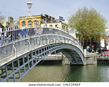 DUBLIN, IRELAND - MAY 25: the Ha'penny Bridge over the River Liffey on May 25, 2013 in Dublin, Ireland. The Ha'penny Bridge is a pedestrian bridge built in 1816 from cast iron. - stock photo