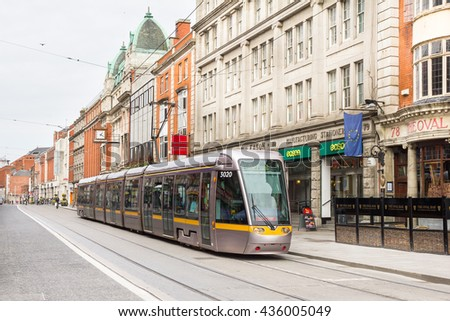DUBLIN, IRELAND - 07 MAY, 2016: Tram crossing a road in the centre of the city. The light rail system has 2 lines, 54 stations and 38.2 km of track and it connects the central area with the suburbs.
