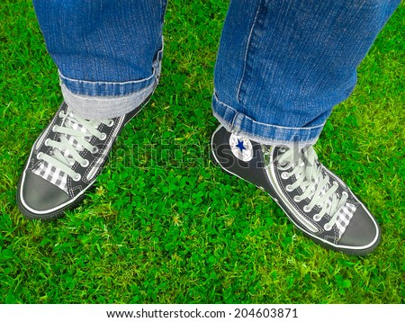 DUBLIN - July 12, 2014: Converse Chuck Taylor All Star custom design black shoes worn by a male person wearing blue jeans.