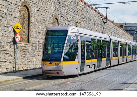 Dublin tram passing in front of stone wall - stock photo