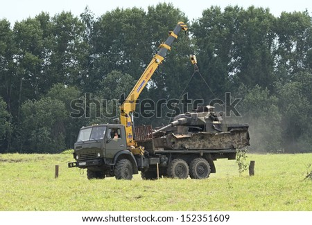 DUBOSEKOVO, RUSSIA - JULY 13: KAMAZ-4310 crane truck loads a wreck of a German WWII tank  during Field of Battle military history festival on July 13, 2013 in Dubosekovo, Russia