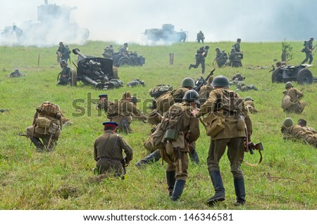 DUBOSEKOVO, RUSSIA - JULY 13: military history club members in Soviet WWII uniform reenact advancement during Field of Battle military history festival on July 13, 2013 in Dubosekovo, Russia  - stock photo