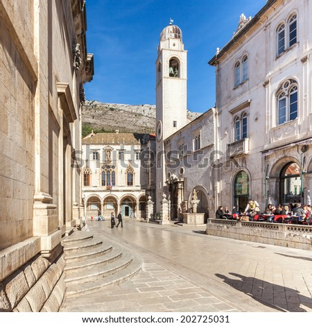DUBROVNIK, CROATIA - JANUARY 14, 2011: Clock tower from 1444, a popular tourist attraction in Dubrovnik Old Town with  Rector's Palace (Knezev dvor) on the left. - stock photo