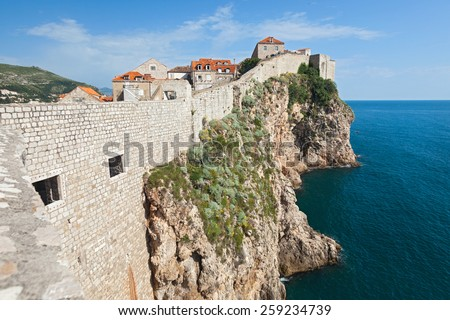 DUBROVNIK, CROATIA - MAY 26, 2014: Old city walls build on cliffs and houses inside the walls. City wall is one of most popular tourist attraction in Dubrovnik. - stock photo