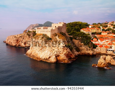 Dubrovnik fortress, Fortress on cliff surrounded by sea and red-tiled houses - stock photo