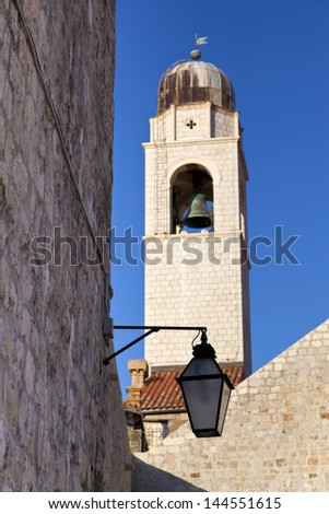 Dubrovnik Sponza Palace's Bell Tower and view of traditional street lamp. Dubrovnik, Croatia - stock photo